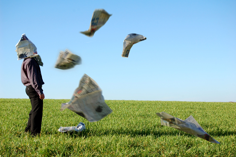 Businessman in a field with newpapers blowing around him hitting him in the face.